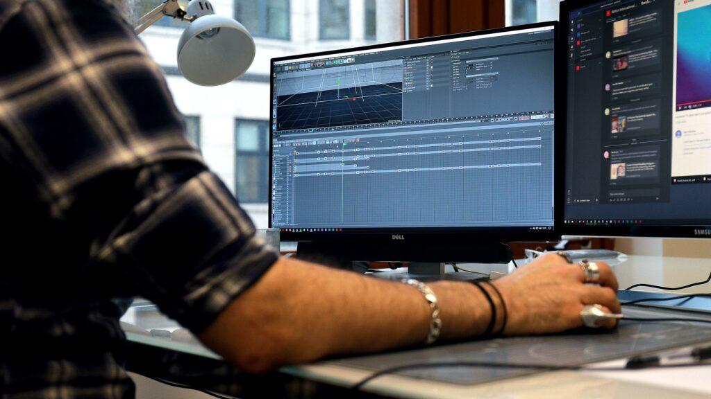 Mitul Rajani working on Cinema 4D on a computer