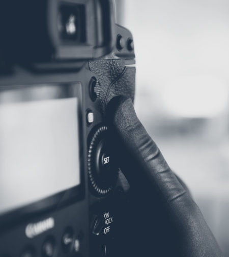 Close-up photograph of a hand wearing disposable gloves operating a Canon camera.